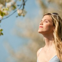 Spring - Young woman under blossom tree enjoy sun
